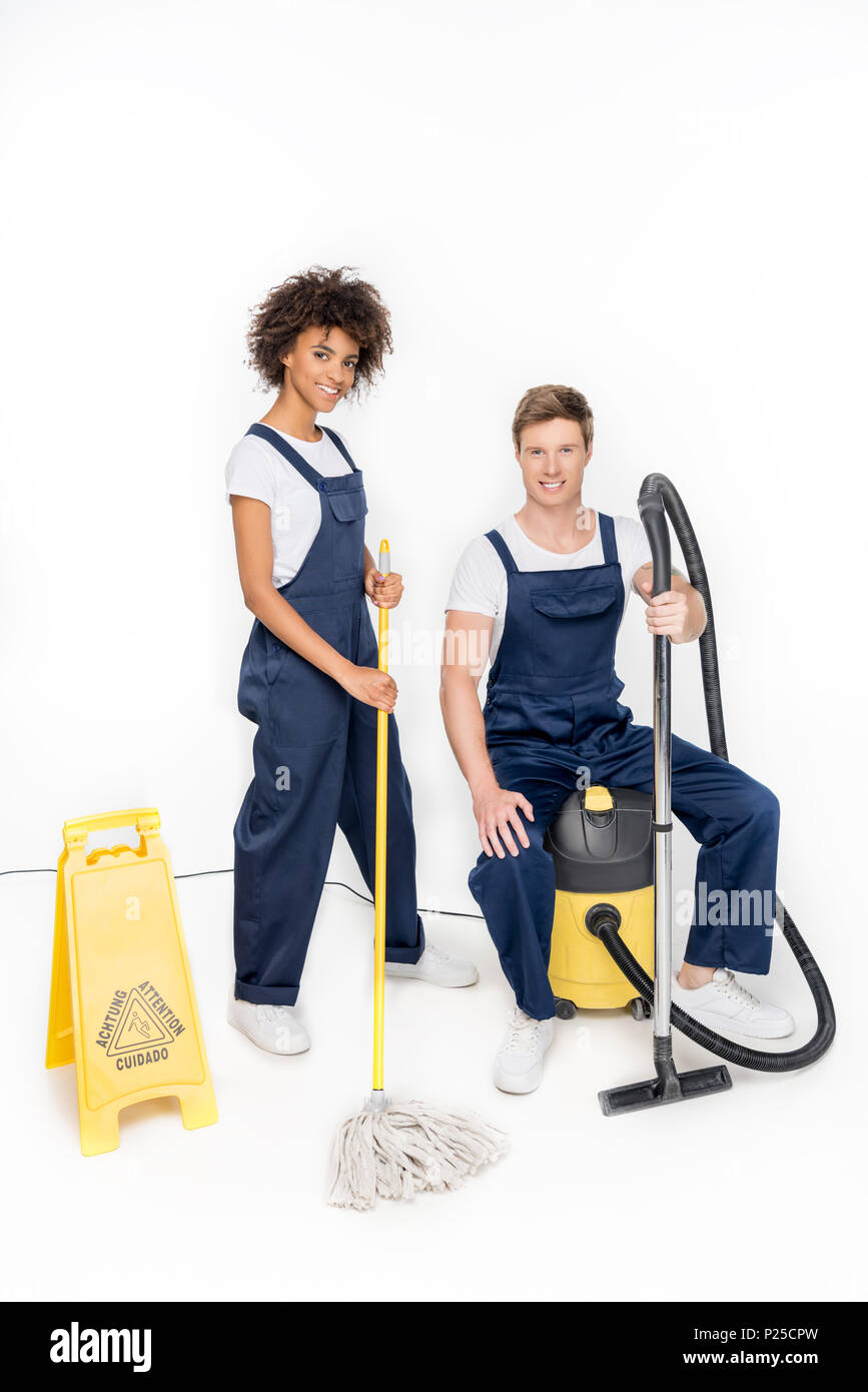 smiling multiethnic cleaners with cleaning supplies and warning sign looking at camera isolated on white - Stock Image