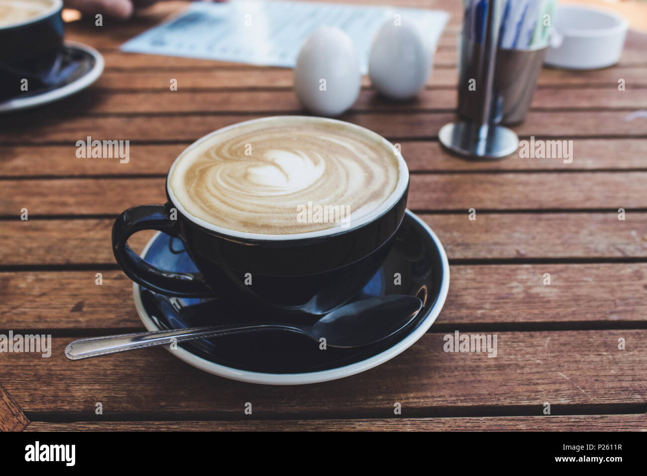 close up image of a hot cup of coffee in a black cup - Stock Image