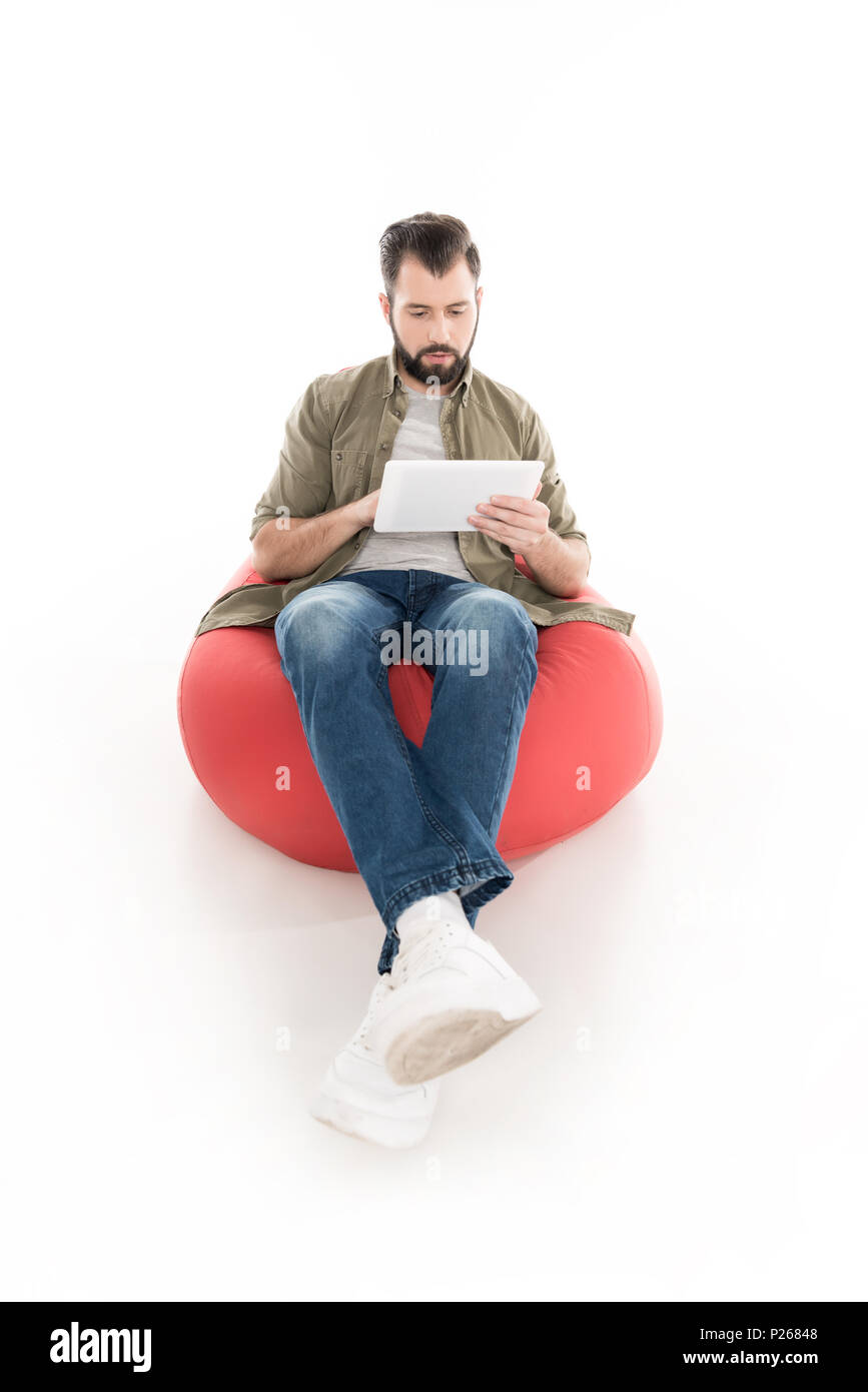 man using digital tablet while sitting on bean bag chair, isolated on white - Stock Image
