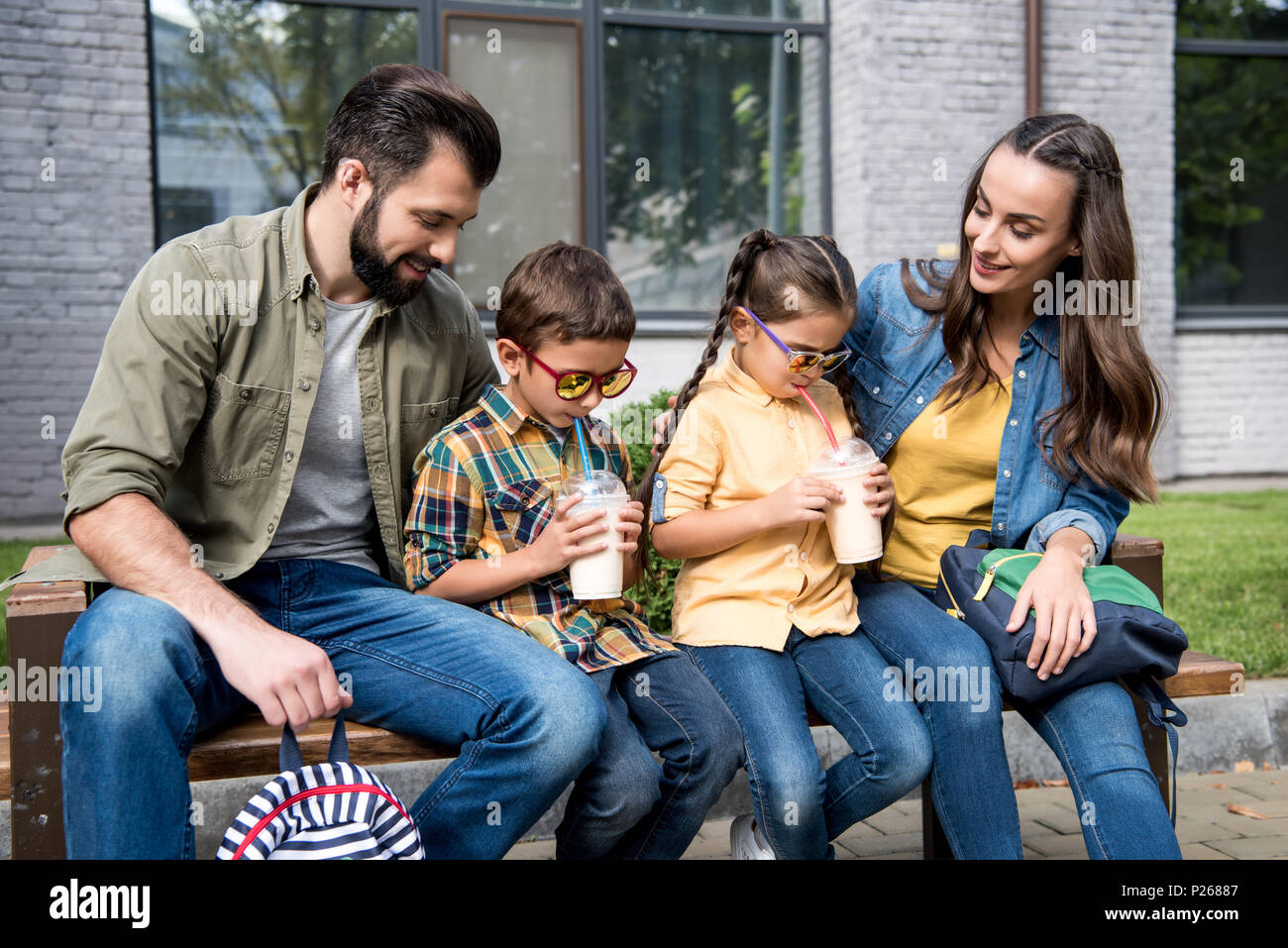 parents and children with milkshakes sitting on bench with backpacks -  Stock Image fbd8dbcc41d9e