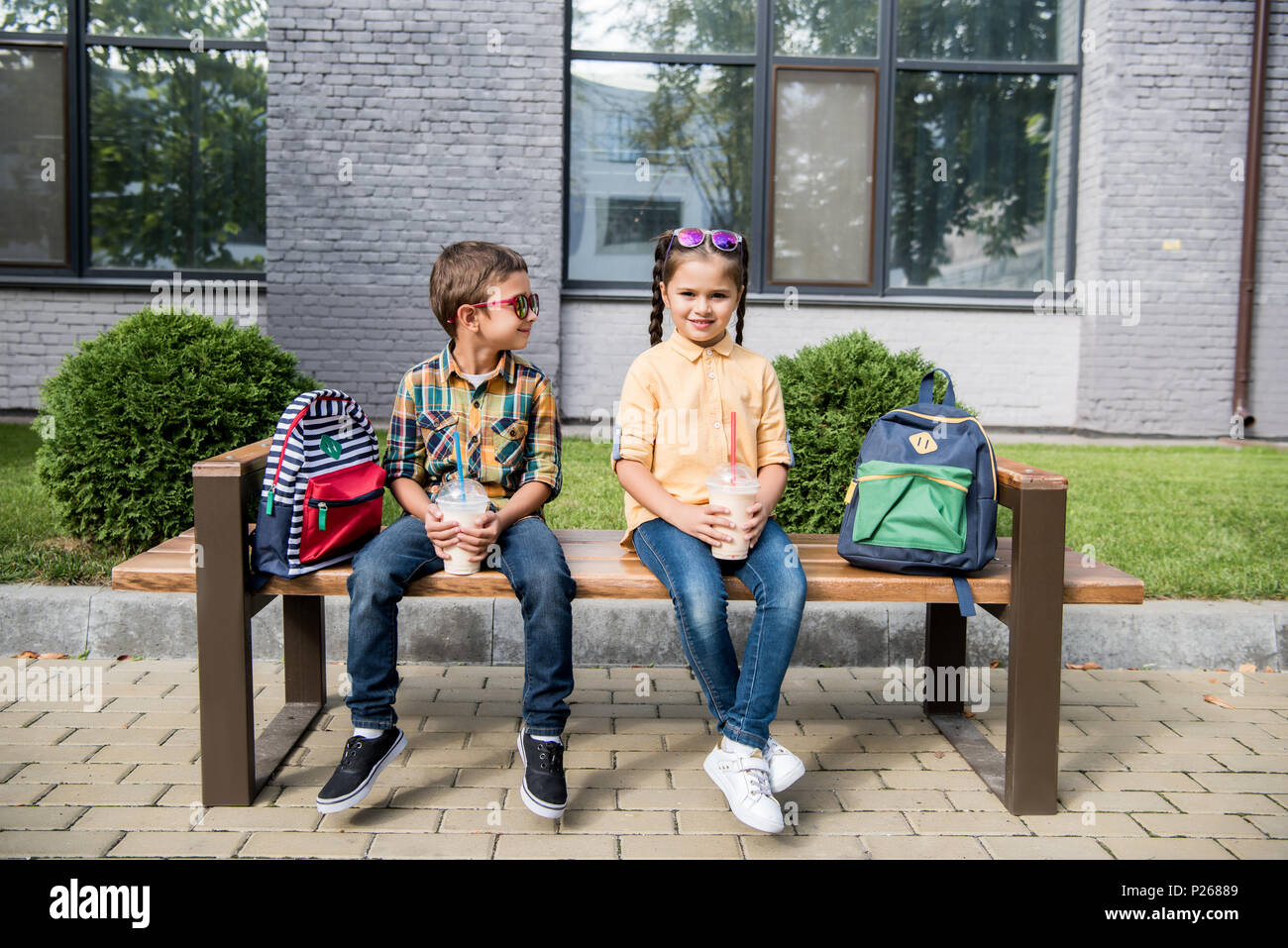 children with milkshakes sitting on bench with backpacks - Stock Image 321c96d188d6c