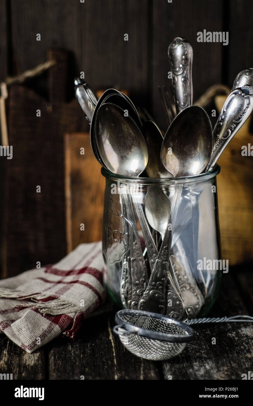 Still life with vintage kitchen utensils: old silver cutlery in a wake-up glass, old sieve, linen and wooden boards - Stock Image