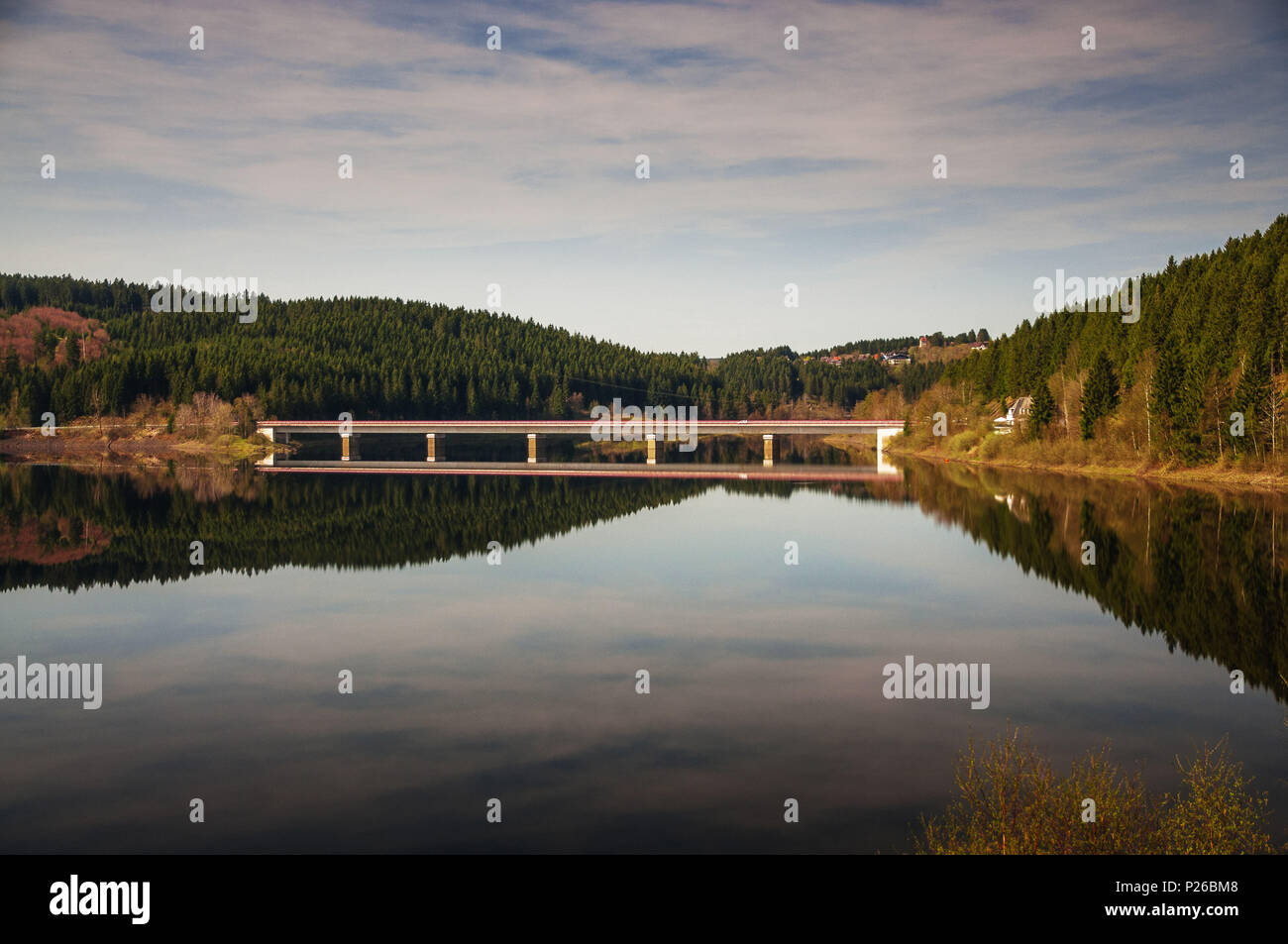 Bridge road over a mountain lake oker dam with perfect water reflections. Okertalsperre, Okerstausee, National Park Harz in Germany - Stock Image
