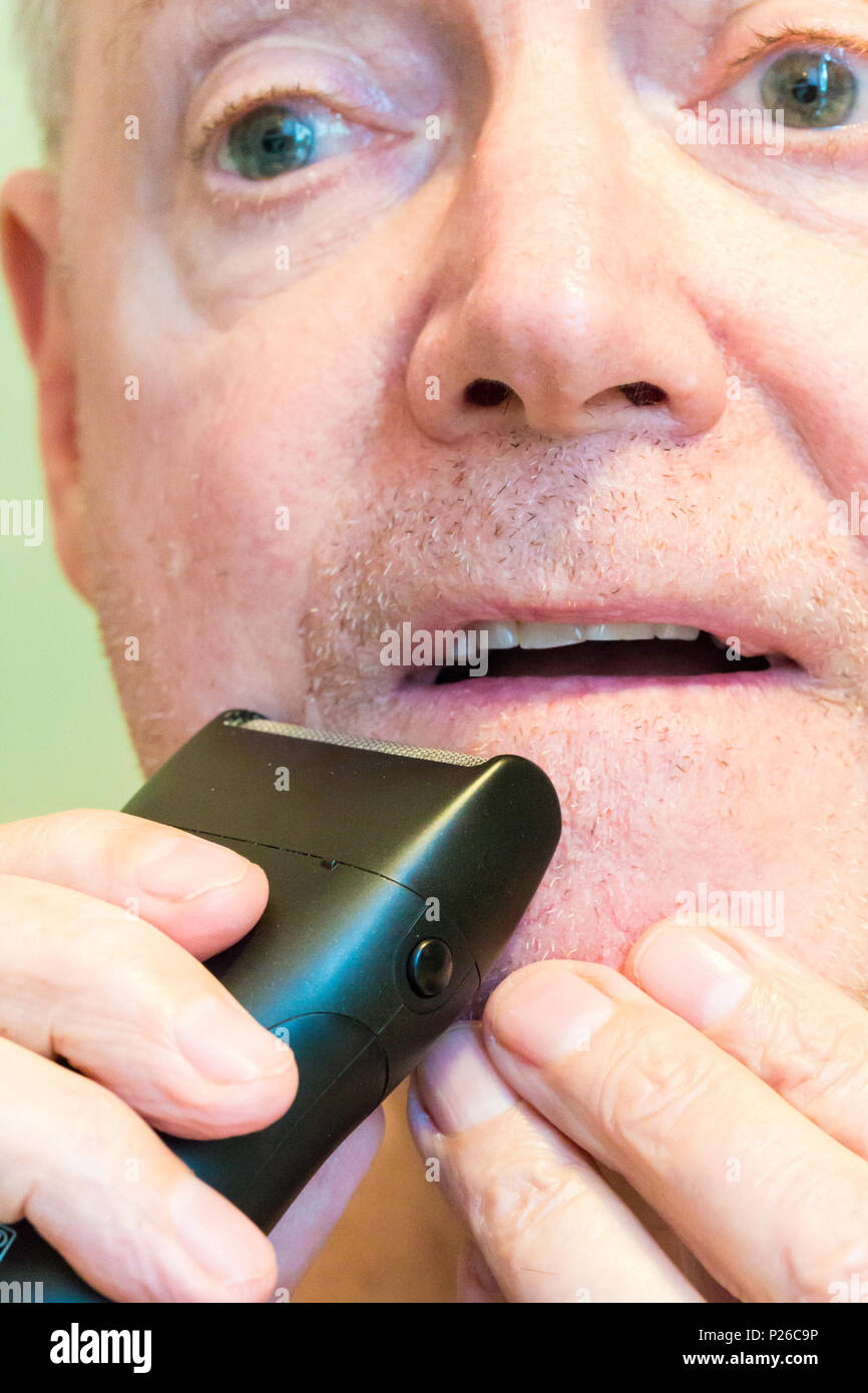 Senior Man Shaving with an Electric Shaver, USA - Stock Image