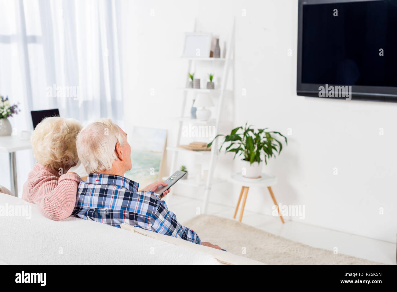 senior couple sitting on comfy couch and watching tv at home - Stock Image