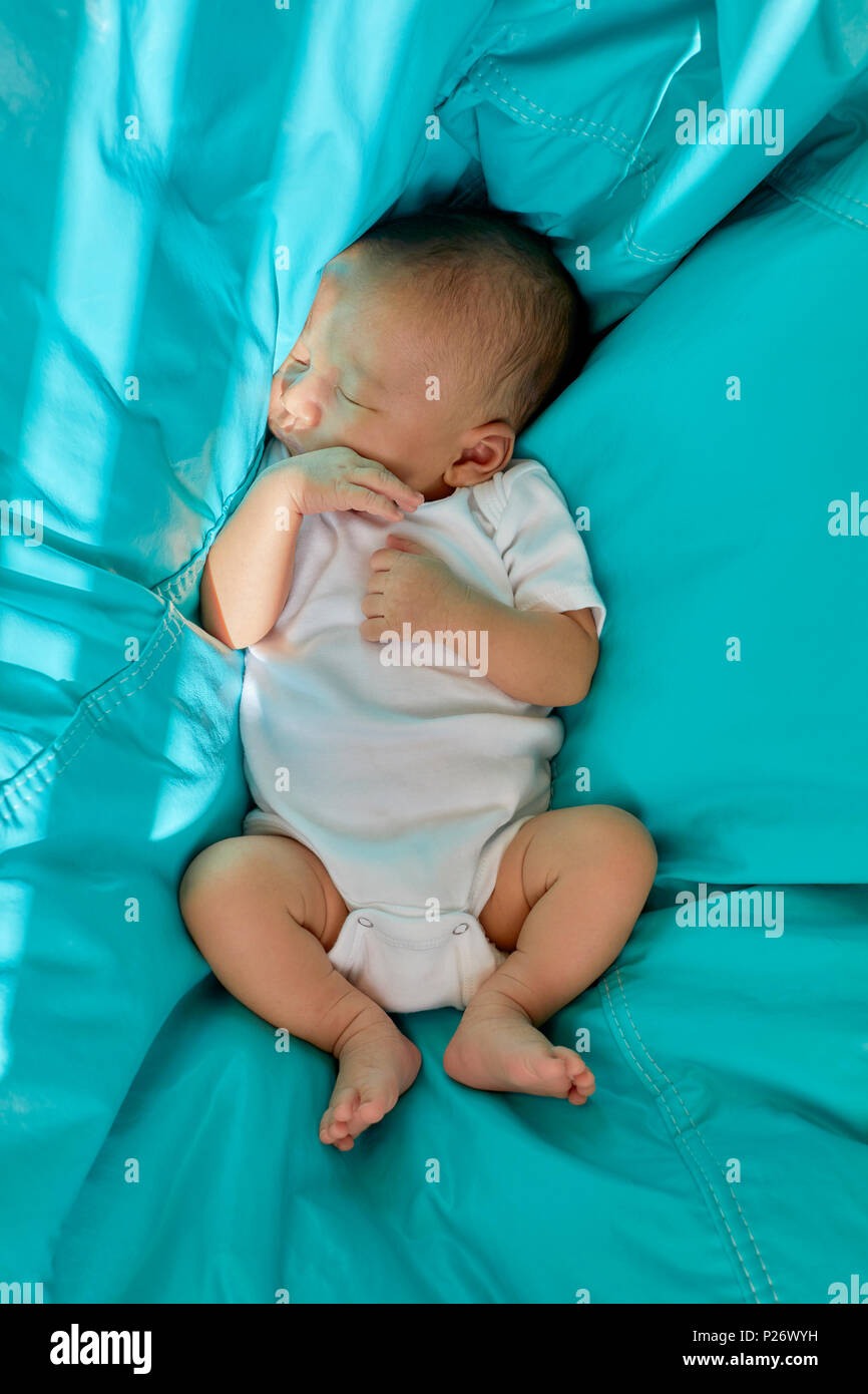 Baby Boy sleeping in a Teal blue bean bag chair - Stock Image