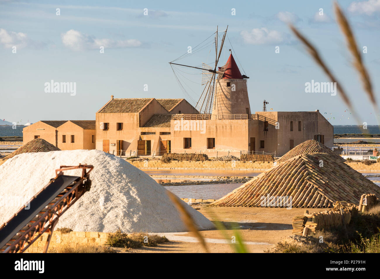 Pyramids of salt in front of Infersa windmill, on the coast connecting Marsala to Trapani, Trapani province, Sicily, Italy - Stock Image