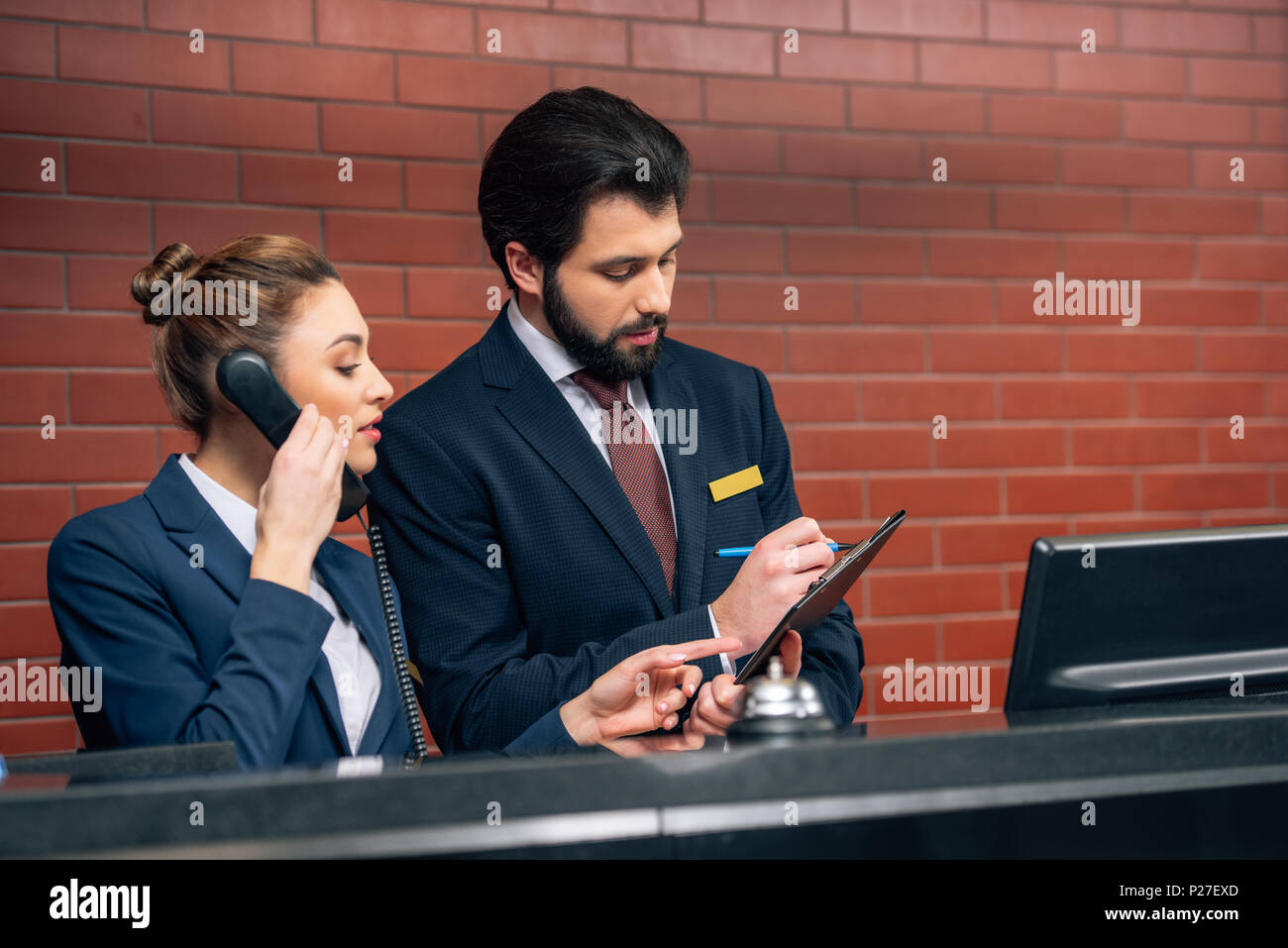 concentrated hotel receptionists receiving call from customer at workplace - Stock Image