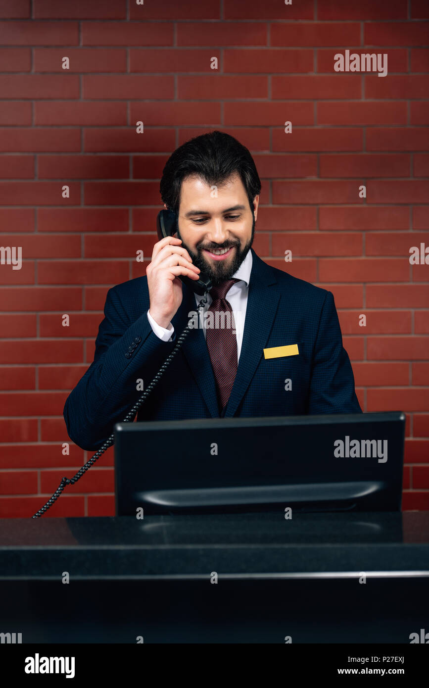 hotel receptionist taking phone call at workplace - Stock Image