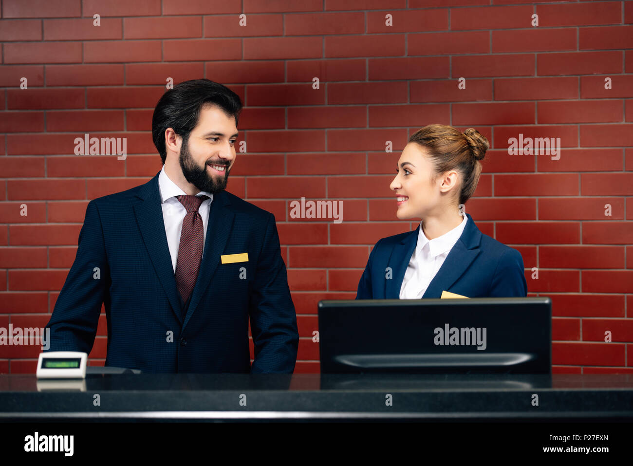 hotel receptionists looking at each other by counter - Stock Image