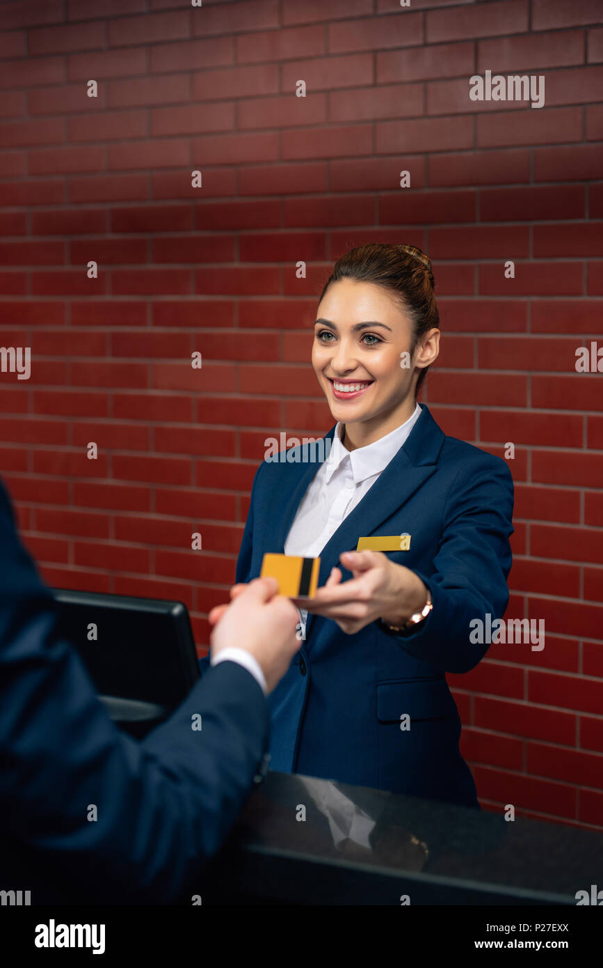 young happy hotel receptionist taking credit card from customer - Stock Image