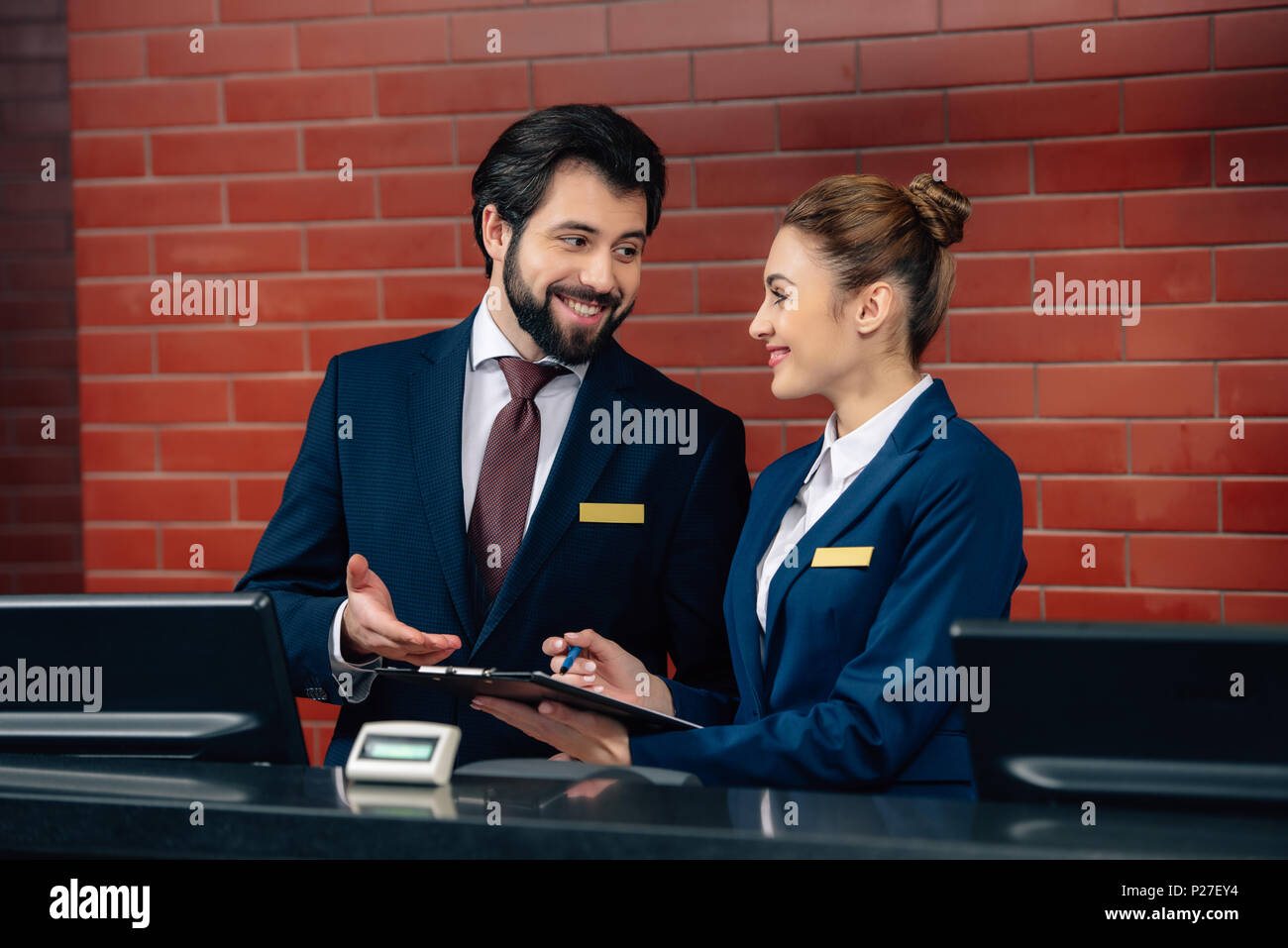 smiling hotel receptionists working together at counter - Stock Image
