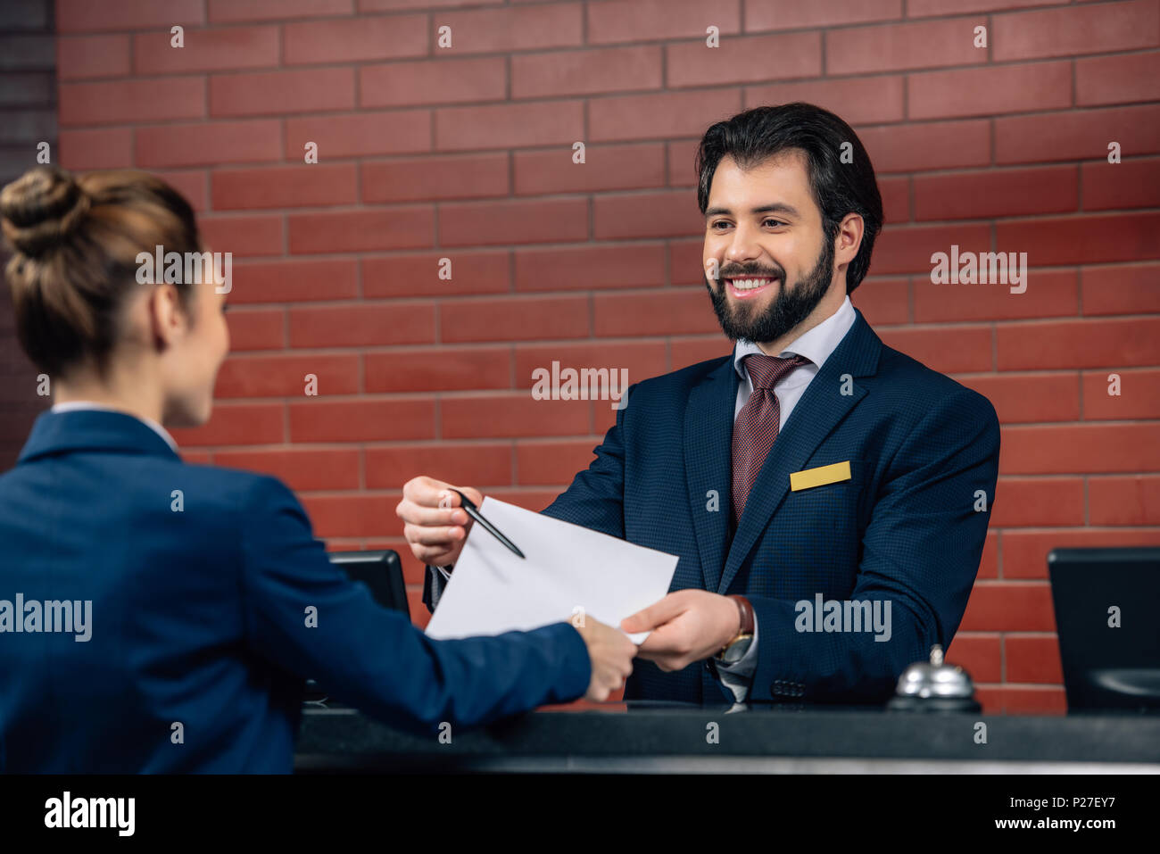 hotel receptionist showing contract customer at counter - Stock Image