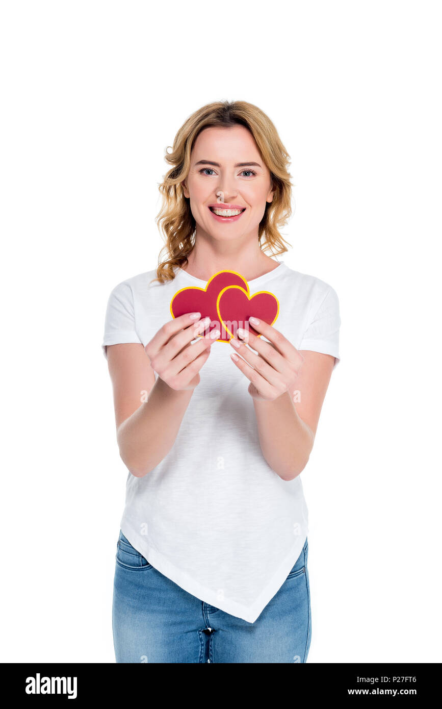 portrait of cheerful woman with heart shaped postcards isolated on white, st valentines day concept - Stock Image