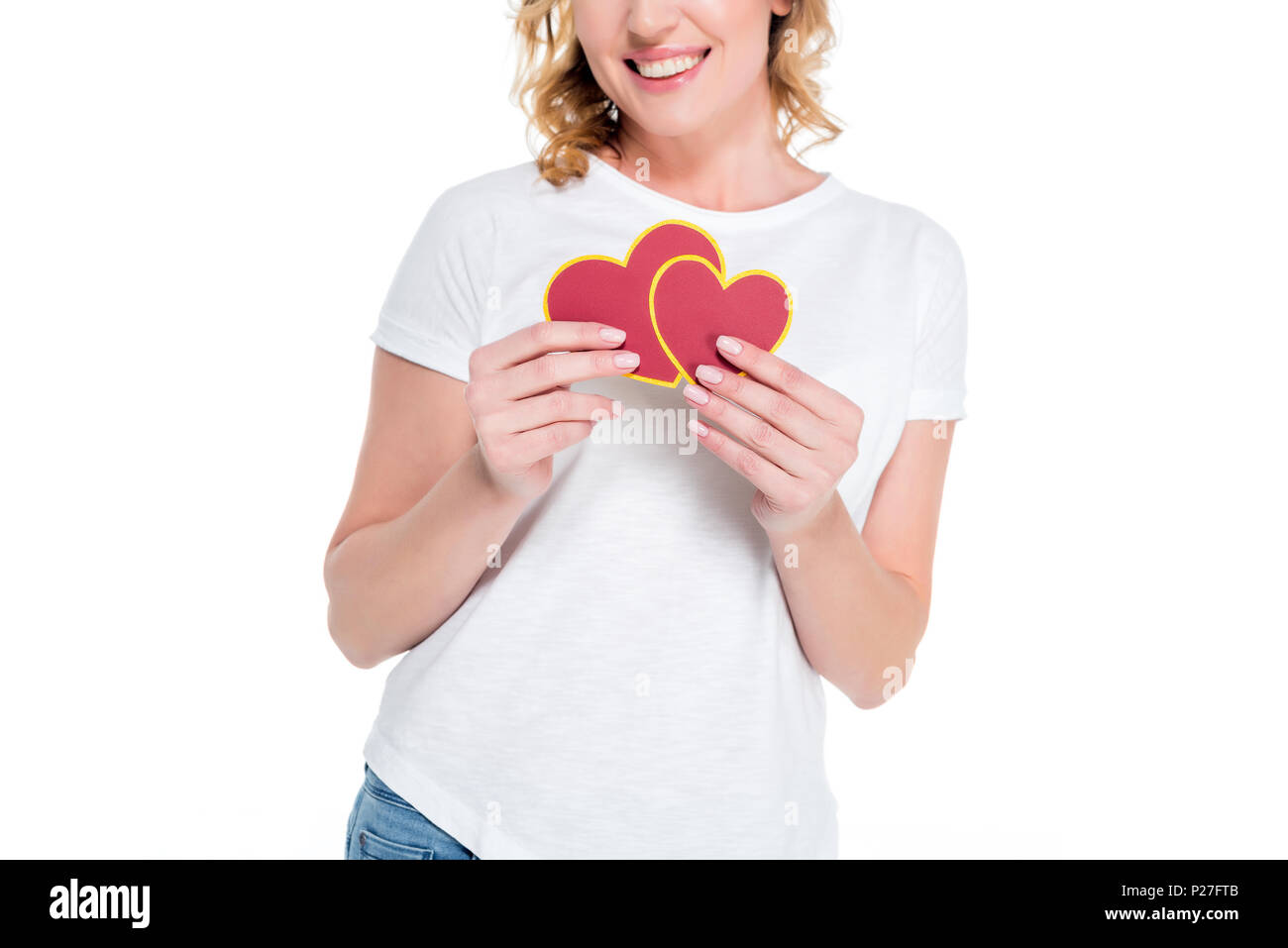 partial view of cheerful woman with heart shaped postcards isolated on white, st valentines day concept - Stock Image
