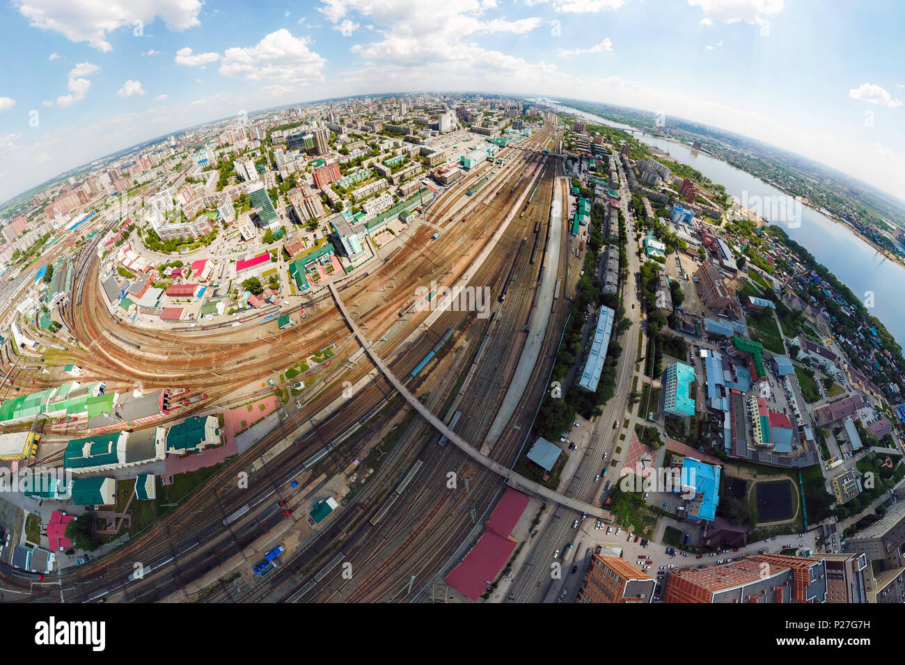 Aerial photography of a modern railroad tracks, trains with wagons on parallel railways, crossings, a railway station, high-rise buildings, a bridge a - Stock Image