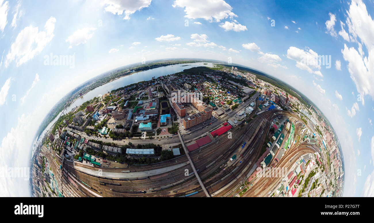 Aerial photography panorama 360 of a modern railroad tracks, trains with wagons on parallel railways, crossings, a railway station, high-rise building - Stock Image
