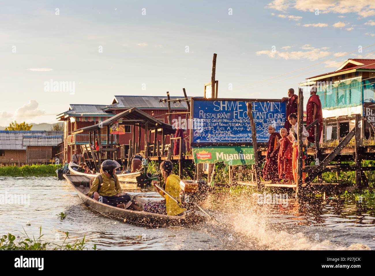 Maing Thauk, wooden bridge into Inle Lake, boat, monks, Inle Lake, Shan State, Myanmar (Burma) - Stock Image
