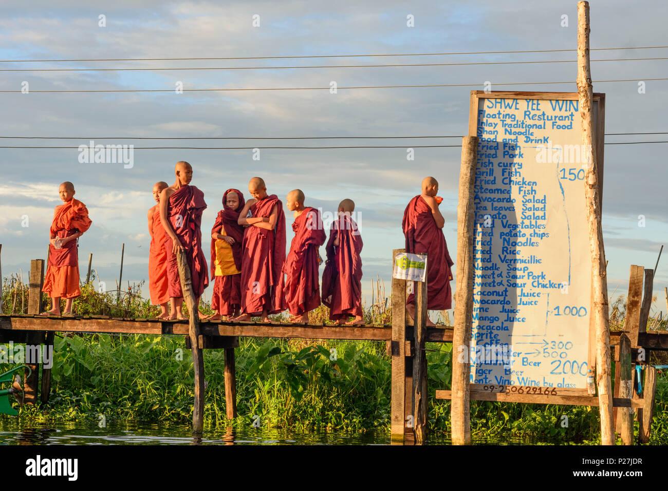 Maing Thauk, wooden bridge into Inle Lake, monks, sign for restaurent, Inle Lake, Shan State, Myanmar (Burma) - Stock Image