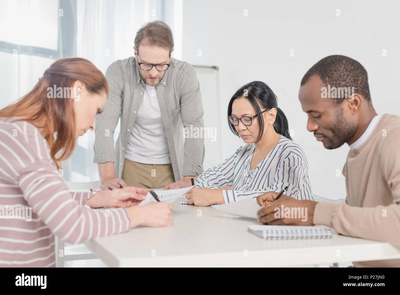multiethnic middle aged business people working with papers together - Stock Image