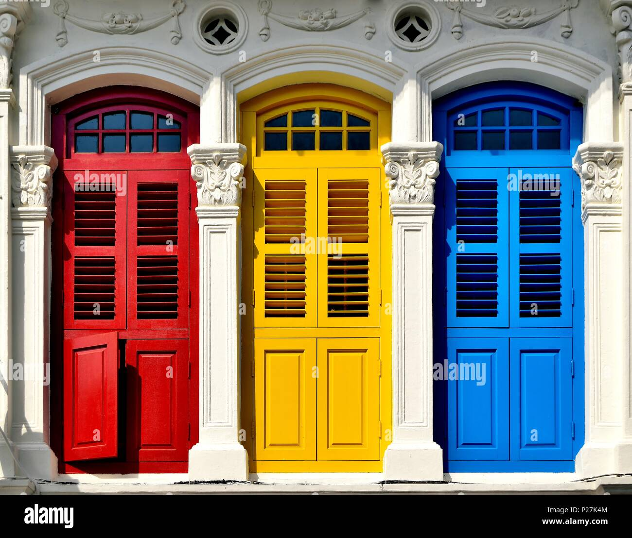 Front view of traditional vintage Singapore shop house or shophouse with antique red, blue and yellow wooden shutters in historic Little India - Stock Image