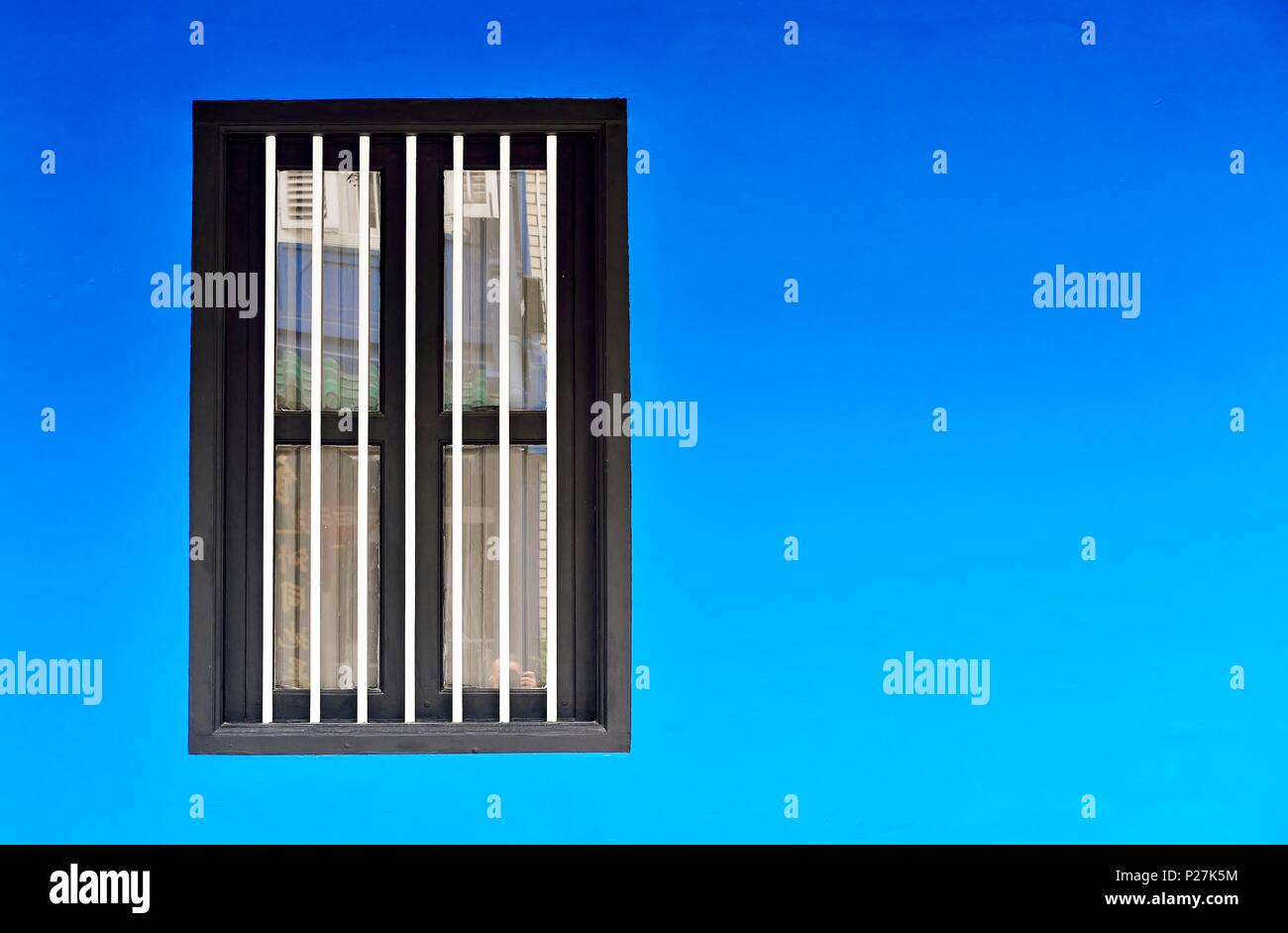 Front view of vintage white wooden shuttered window on the weathered blue exterior of an old Singapore shophouse with space for copy. - Stock Image