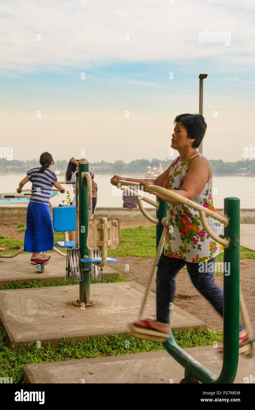 Yangon (Rangoon), woman at work out training machine, Yangon River, Yangon Region, Myanmar (Burma) - Stock Image