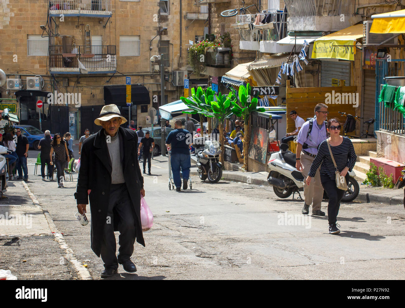 9 May 2018 An aged man in a long dark coat and floppy hat making his way up a hill at the busy Mahane Yehuda street market in Jerusalem Israel - Stock Image