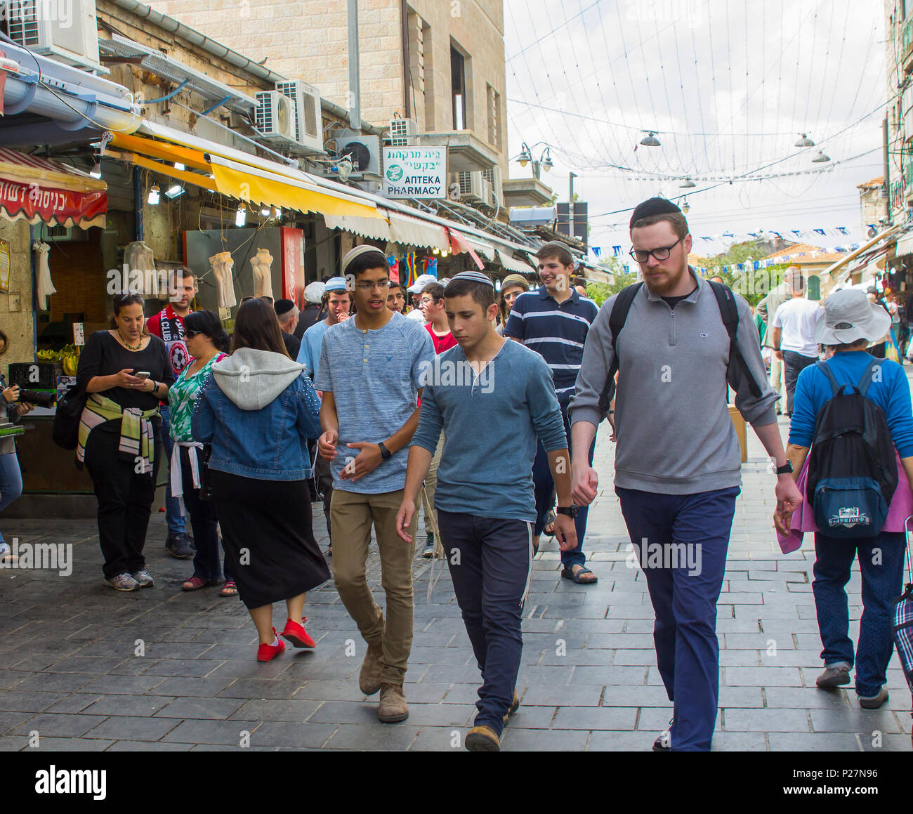 9 May 2018 Male Jewish students wearing skull caps and in conversation as they make their way through the busy Mahane Yehuda  market in Jerusalem - Stock Image