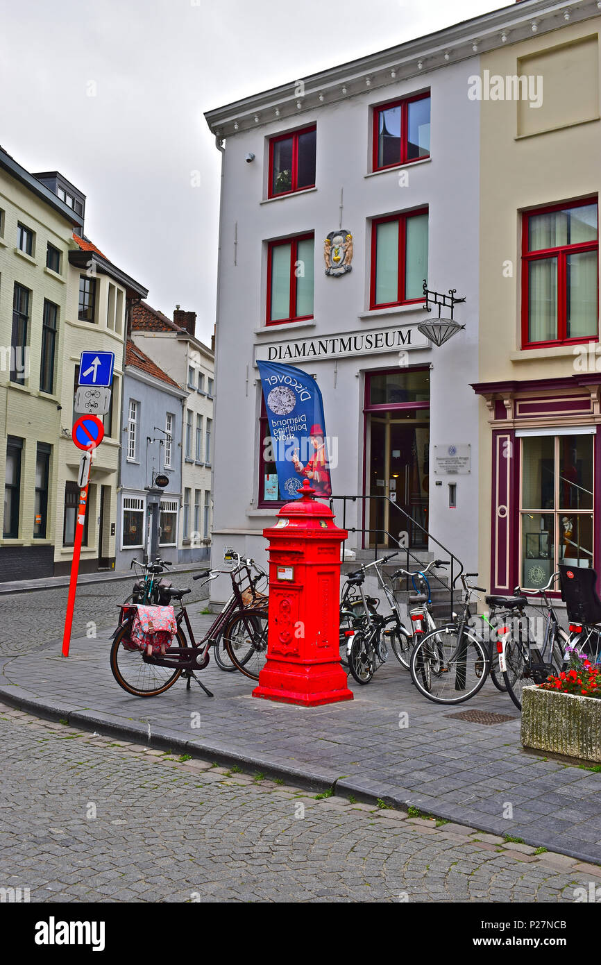 A small square in the centre of Bruges or Brugge with a bright red post box and the famous Diamant (Diamond) Museum behind, Belgium,EU - Stock Image