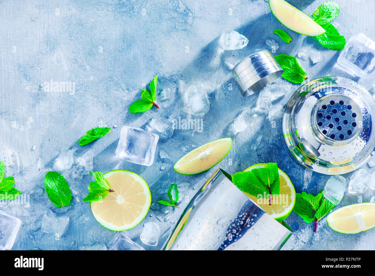 Shaker and bar accessories flat lay. Fresh mojito cocktail ingredients, mint, lime and ice cubes on a gray stone background. Summer drink concept with Stock Photo