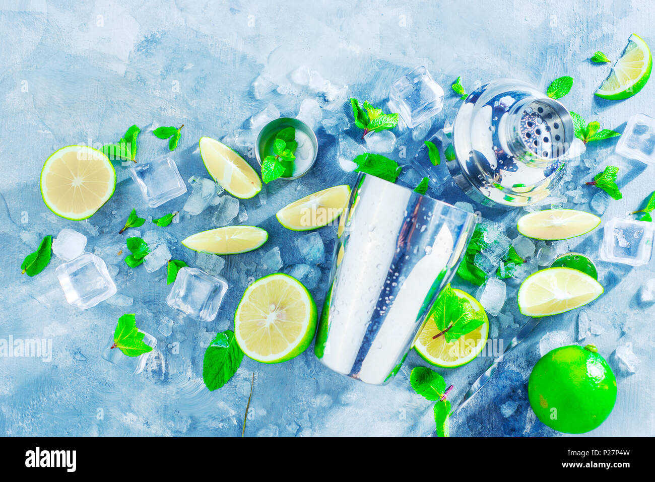 Shaker and bar accessories flat lay. Fresh mojito cocktail ingredients, mint, lime and ice cubes on a gray stone background. Summer drink concept with - Stock Image