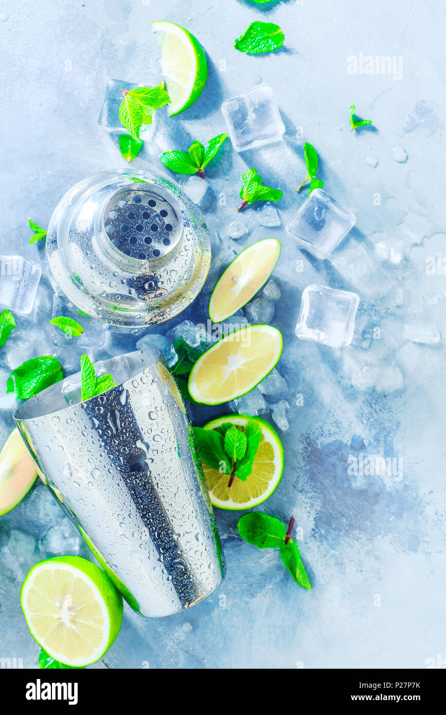 Shaker and bar accessories close-up. Mojito cocktail ingredients, mint, lime and ice cubes on a gray stone background. Summer drink concept with copy  - Stock Image