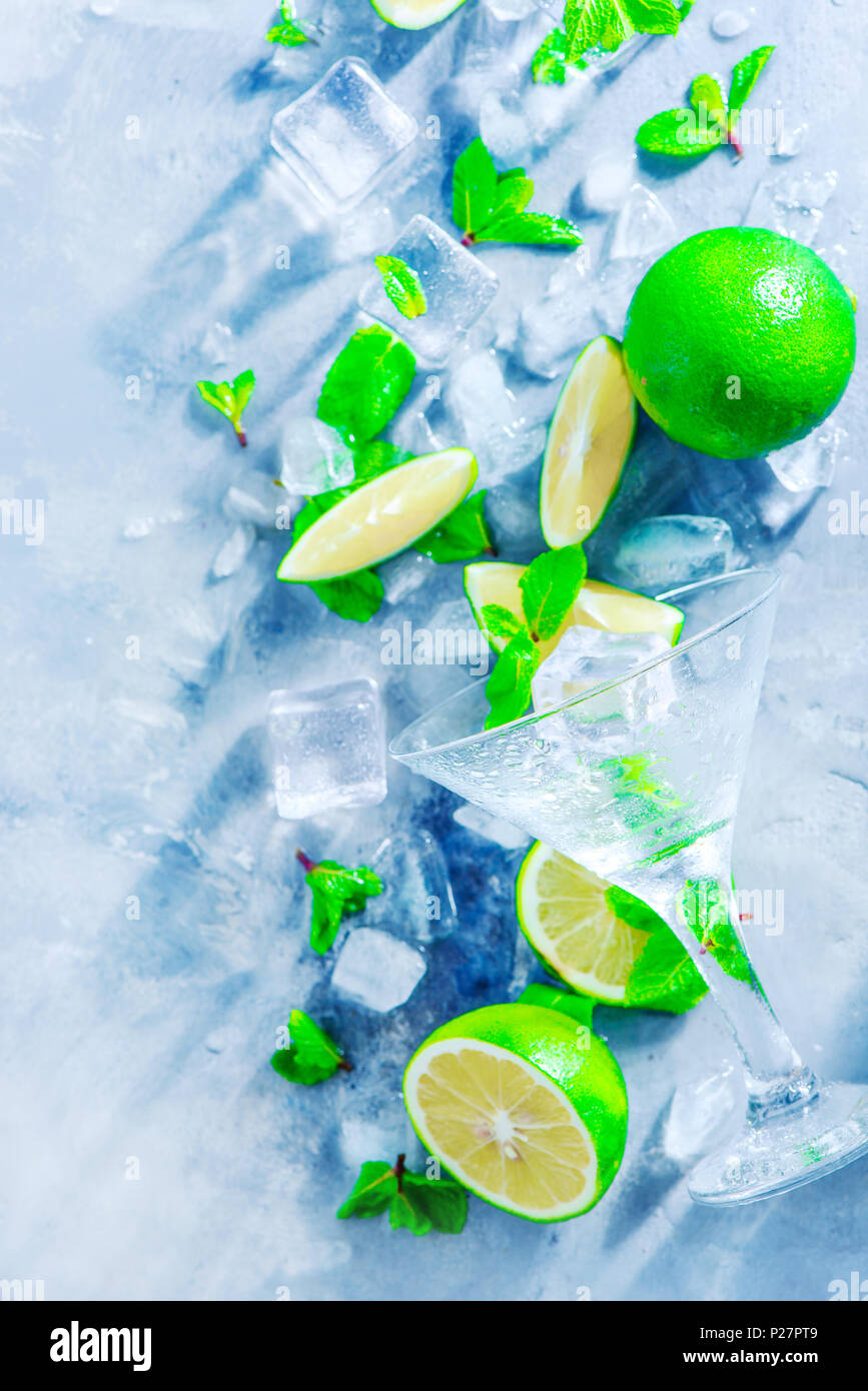 Mint, lime and ice cubes on a gray stone background with copy space. Making summer drinks flat lay. Sunlight and refreshment concept with cocktail gla - Stock Image