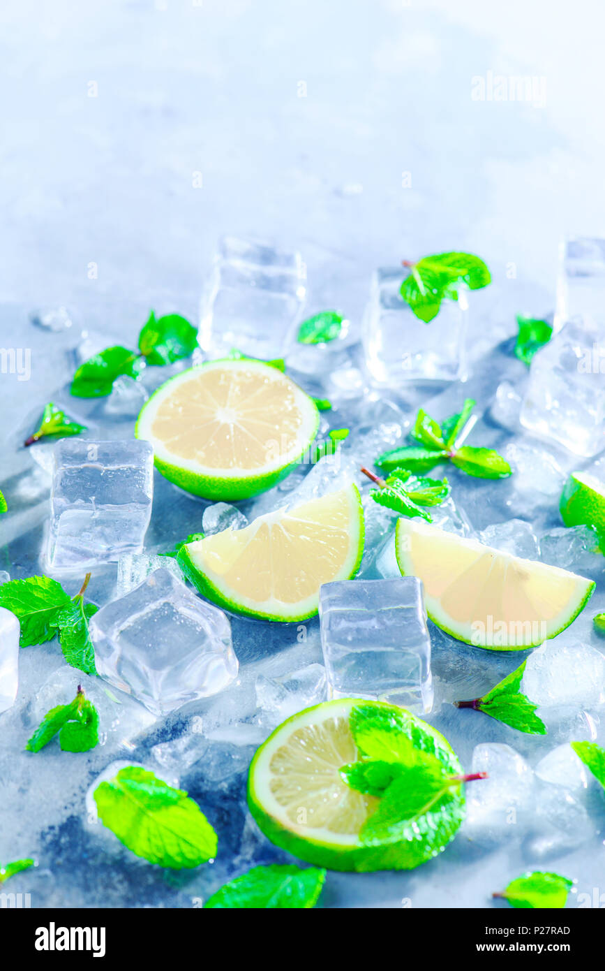 Mint, lime and ice cubes, mojito cocktail ingredients close-up with copy space. Making summer drinks close-up. Sunlight and refreshment concept. - Stock Image
