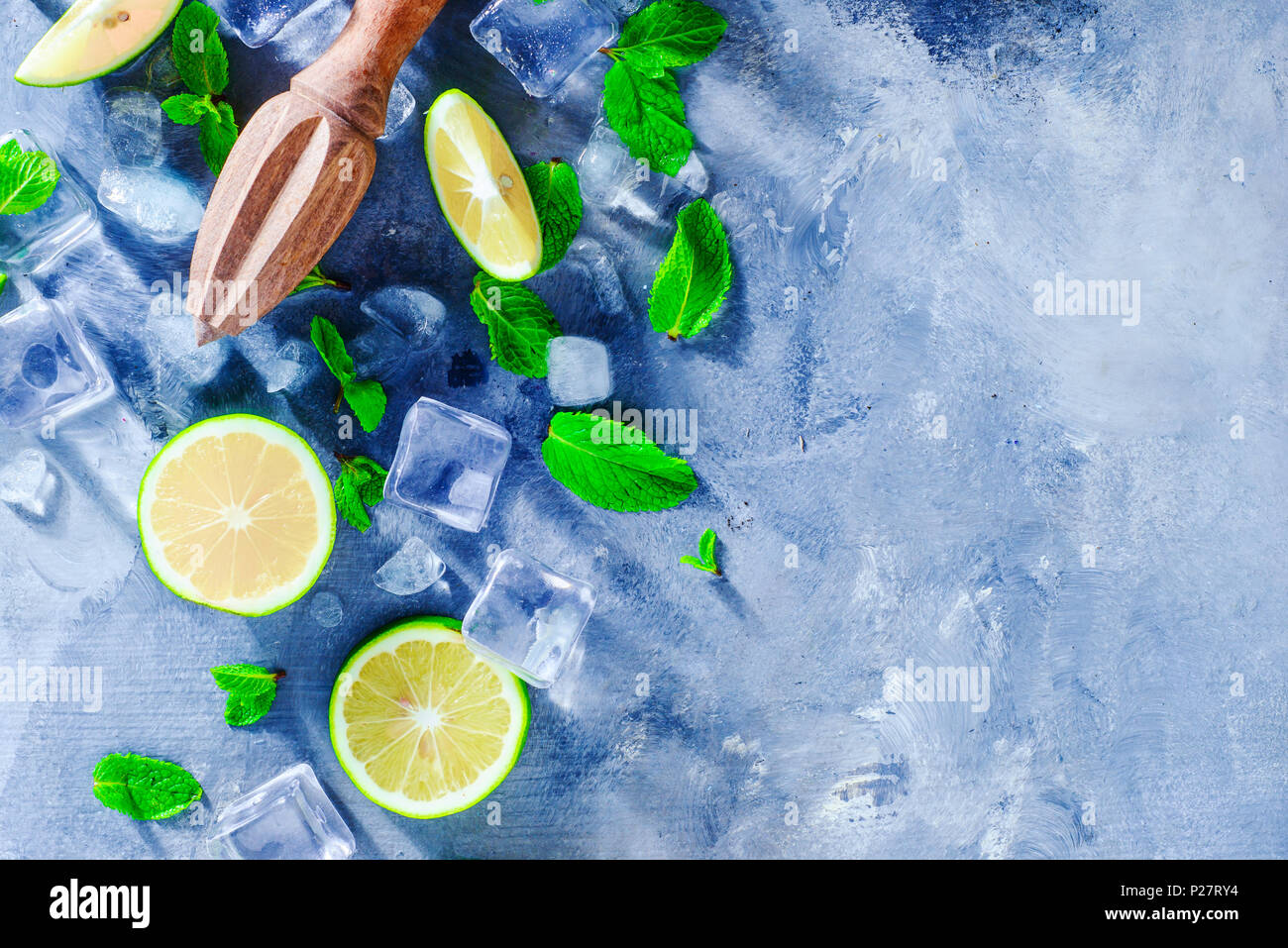 Summer drink header with mojito cocktail ingredients, mint, lime and ice cubes. Lemon reamer or juicer on a gray stone background with copy space. - Stock Image