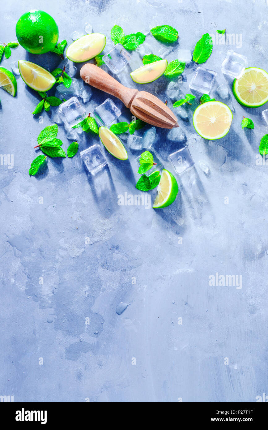 Lemon reamer or juicer with mint, lime and ice cubes. Mojito cocktail ingredients on a gray stone background with copy space. Summer drink concept sun - Stock Image