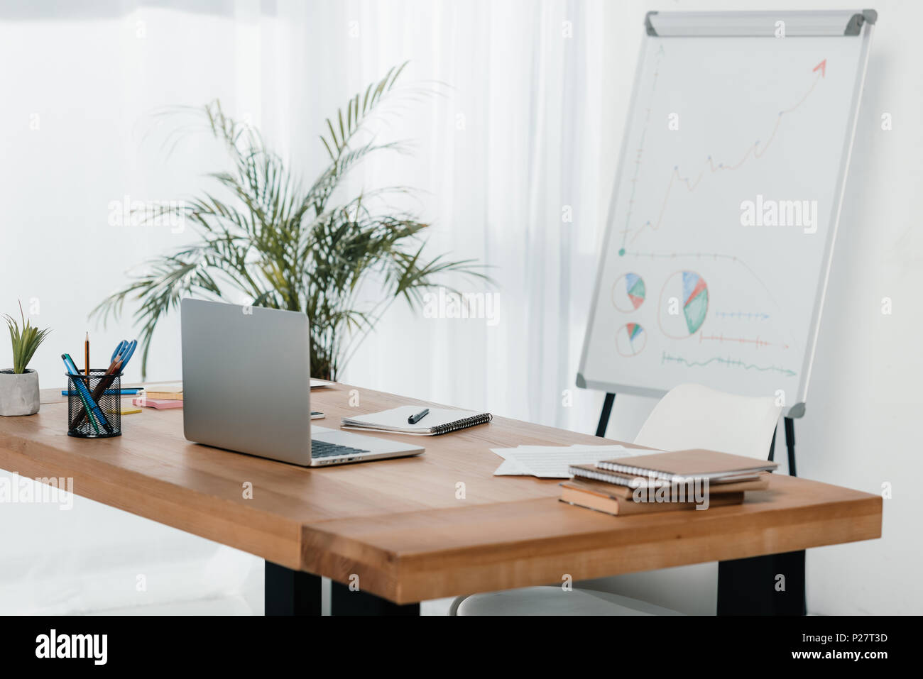 workplace with laptop and office supplies in office with white board - Stock Image