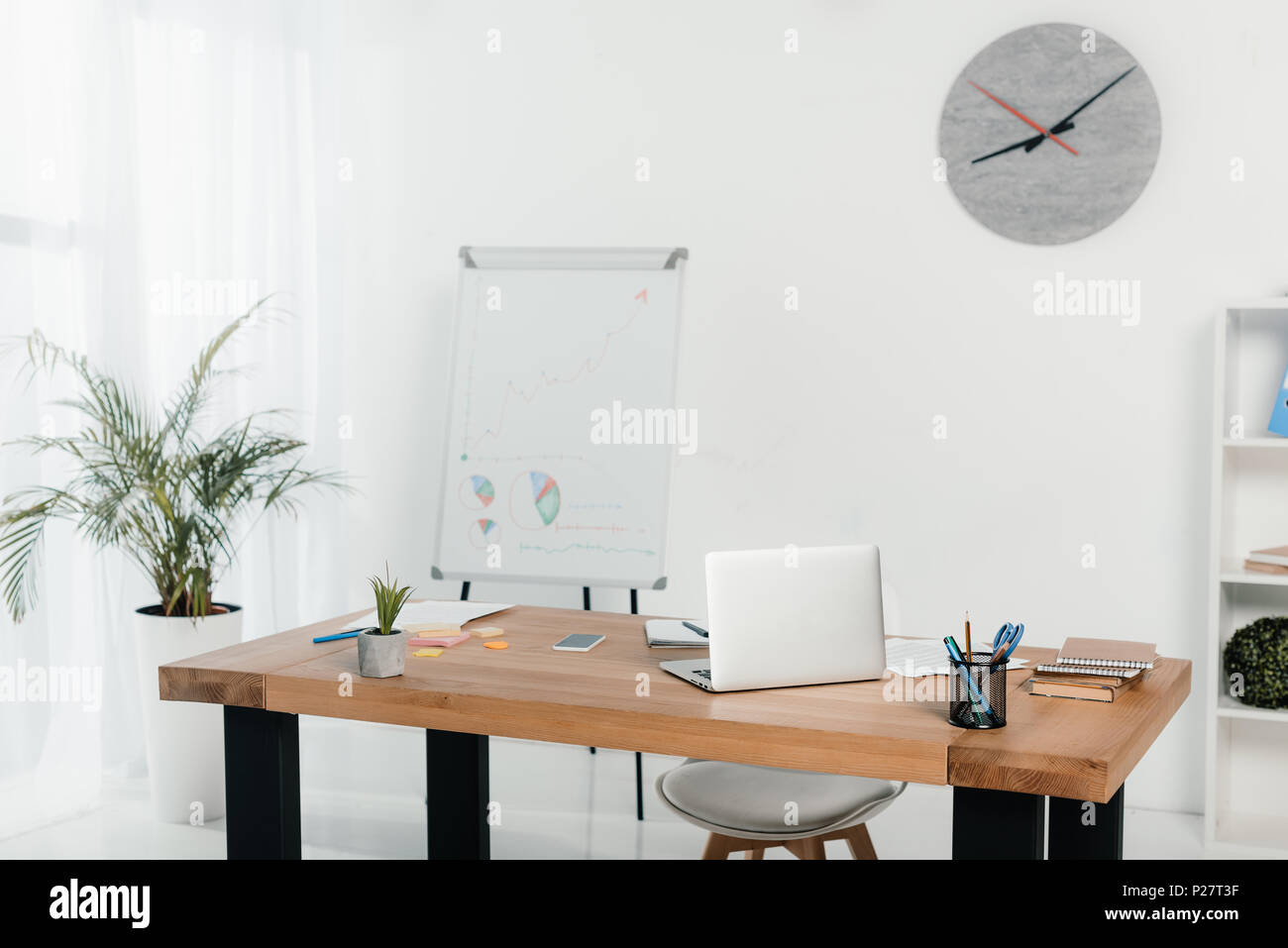 workplace with laptop and office supplies in office with white board and clock - Stock Image