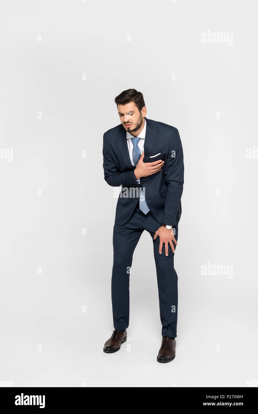 stressed overworked businessman having heartache isolated on grey - Stock Image