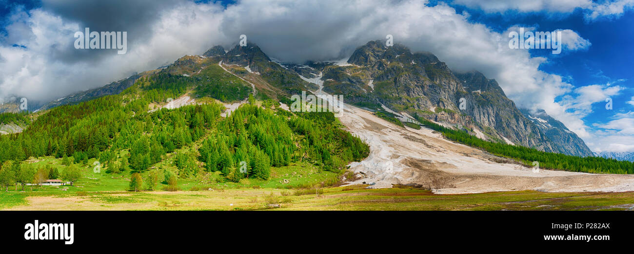 Landscape in spring season in the Ferret valley with avalanche in foreground and clouds and blue sky in background, Courmayeur - Italy - Stock Image