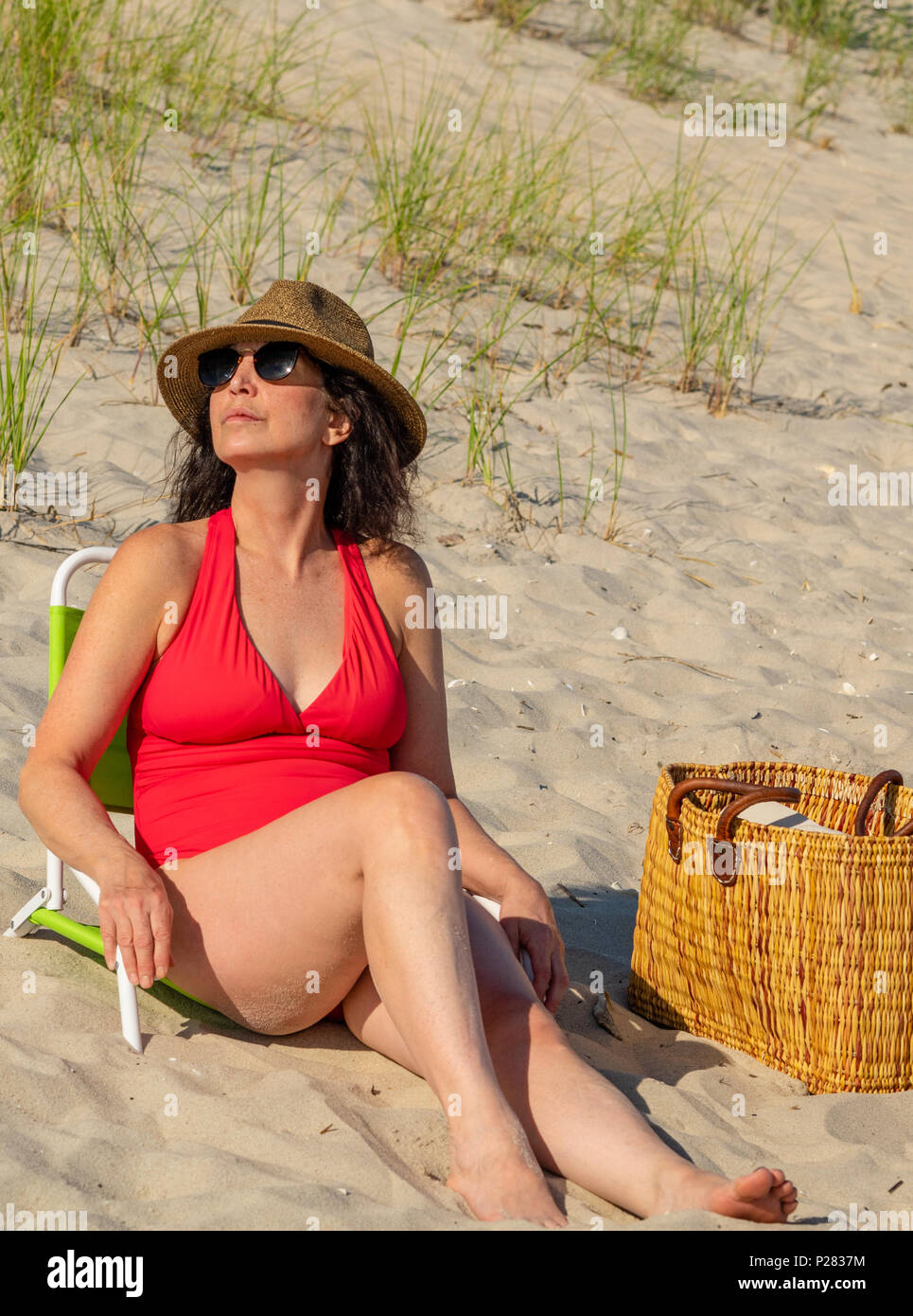 Woman in bathing suit relaxing on beach. - Stock Image