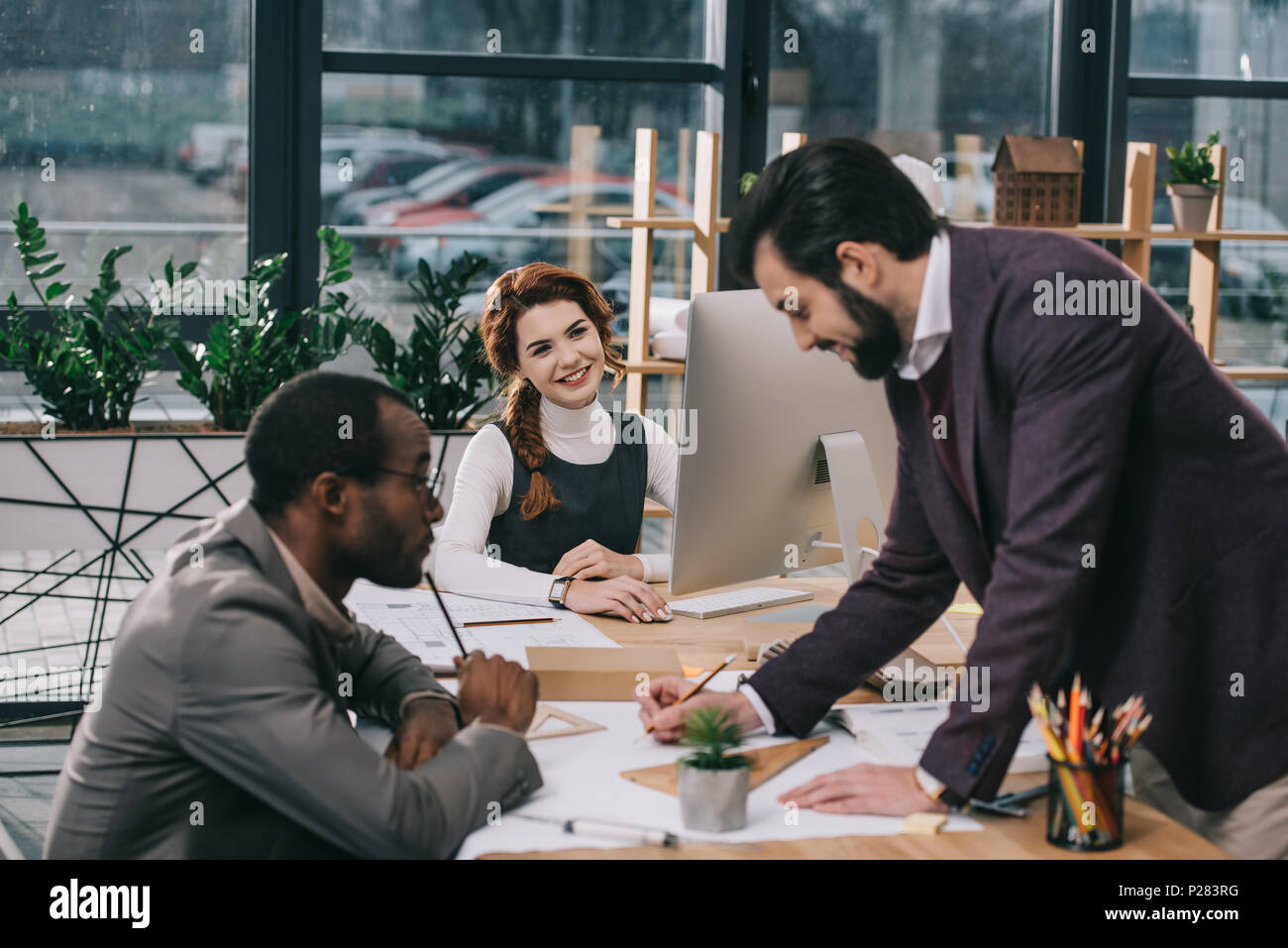multiethnic architects discussing blueprints in modern office - Stock Image