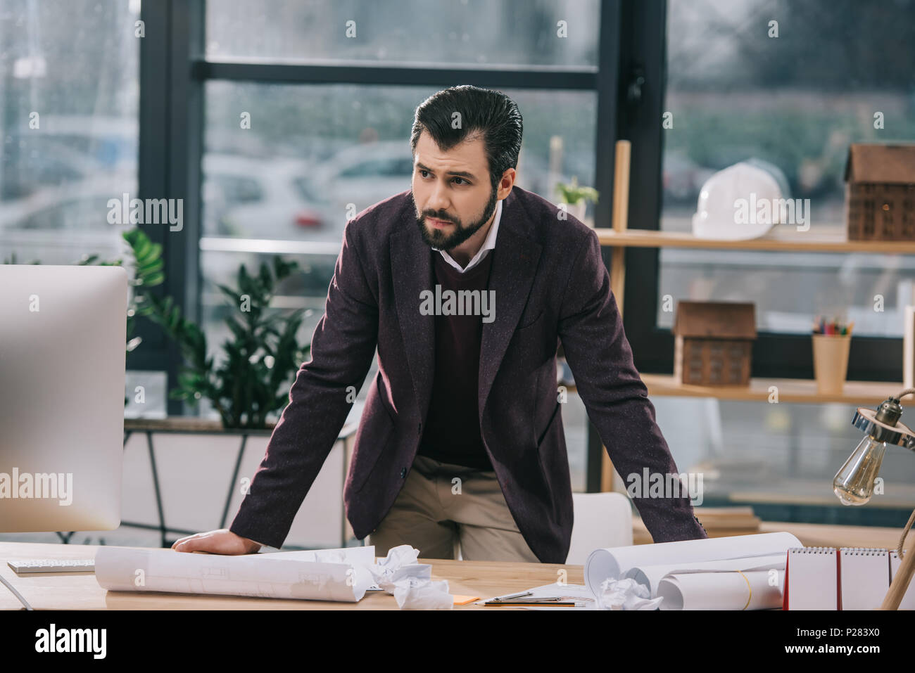 thoughtful male architect at workspace with blueprints and crumpled papers - Stock Image