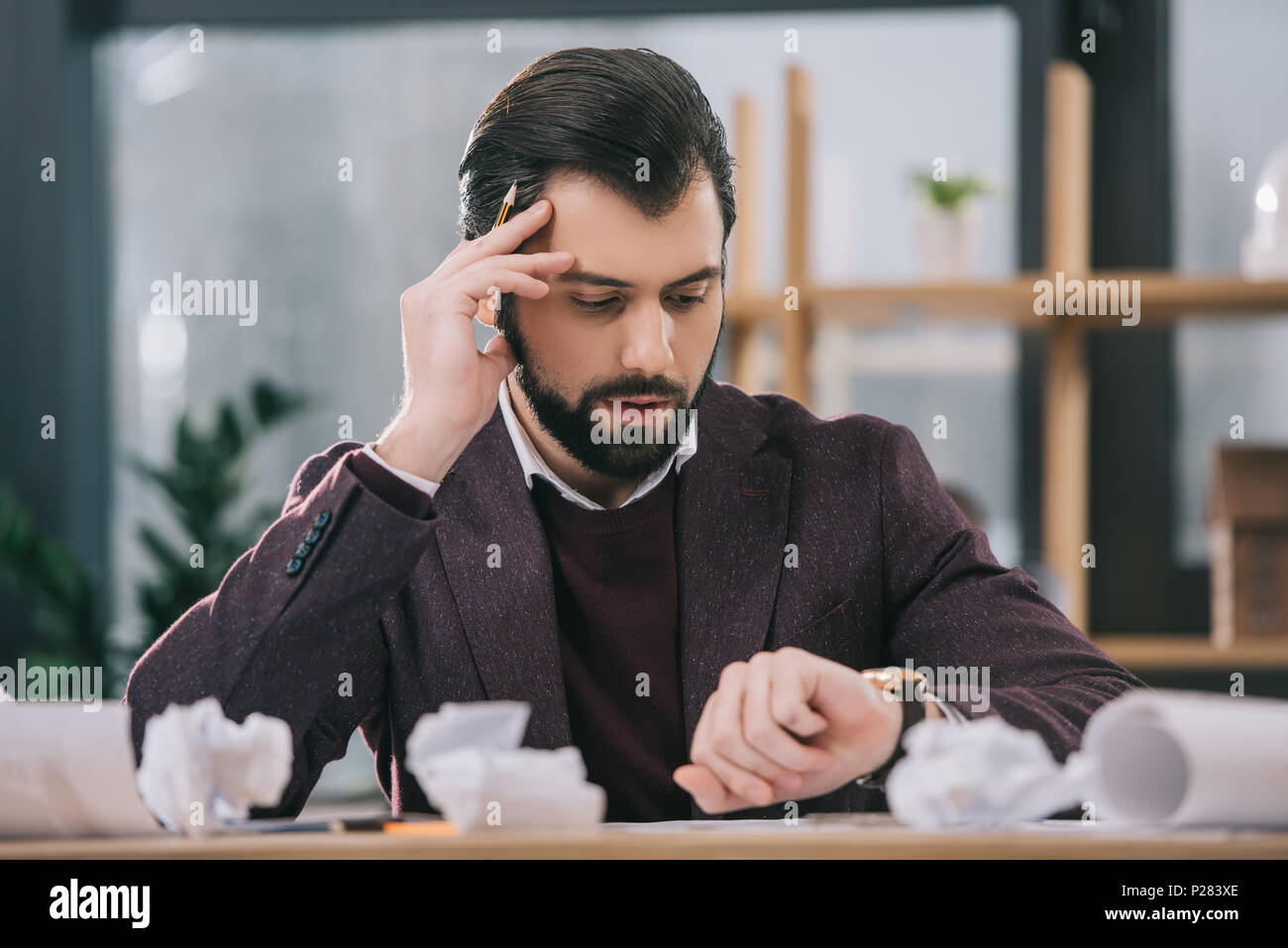 worried architect drawing building plans at workplace with crumpled papers - Stock Image