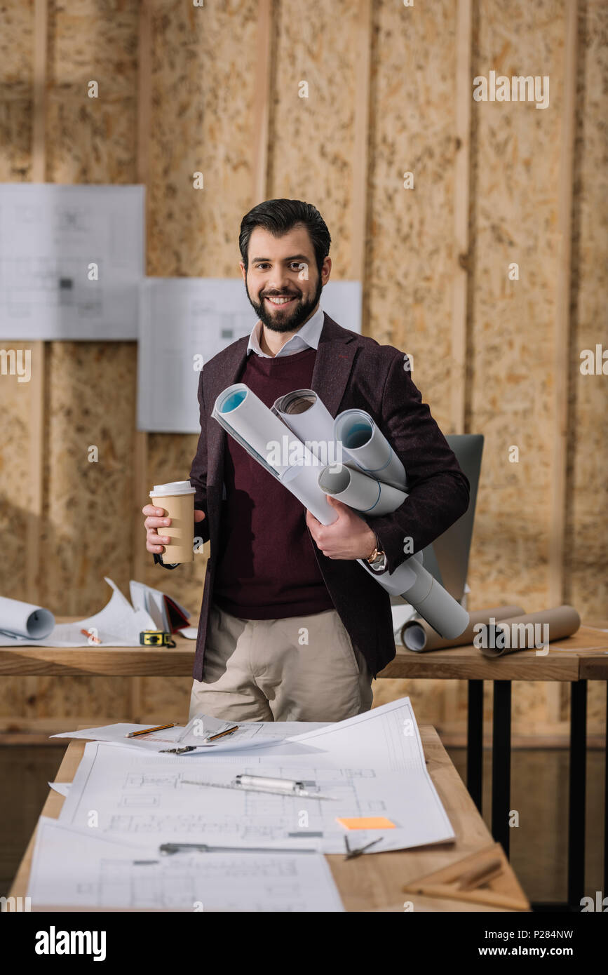 young architect with coffee to go and rolled blueprints at workplace Stock Photo