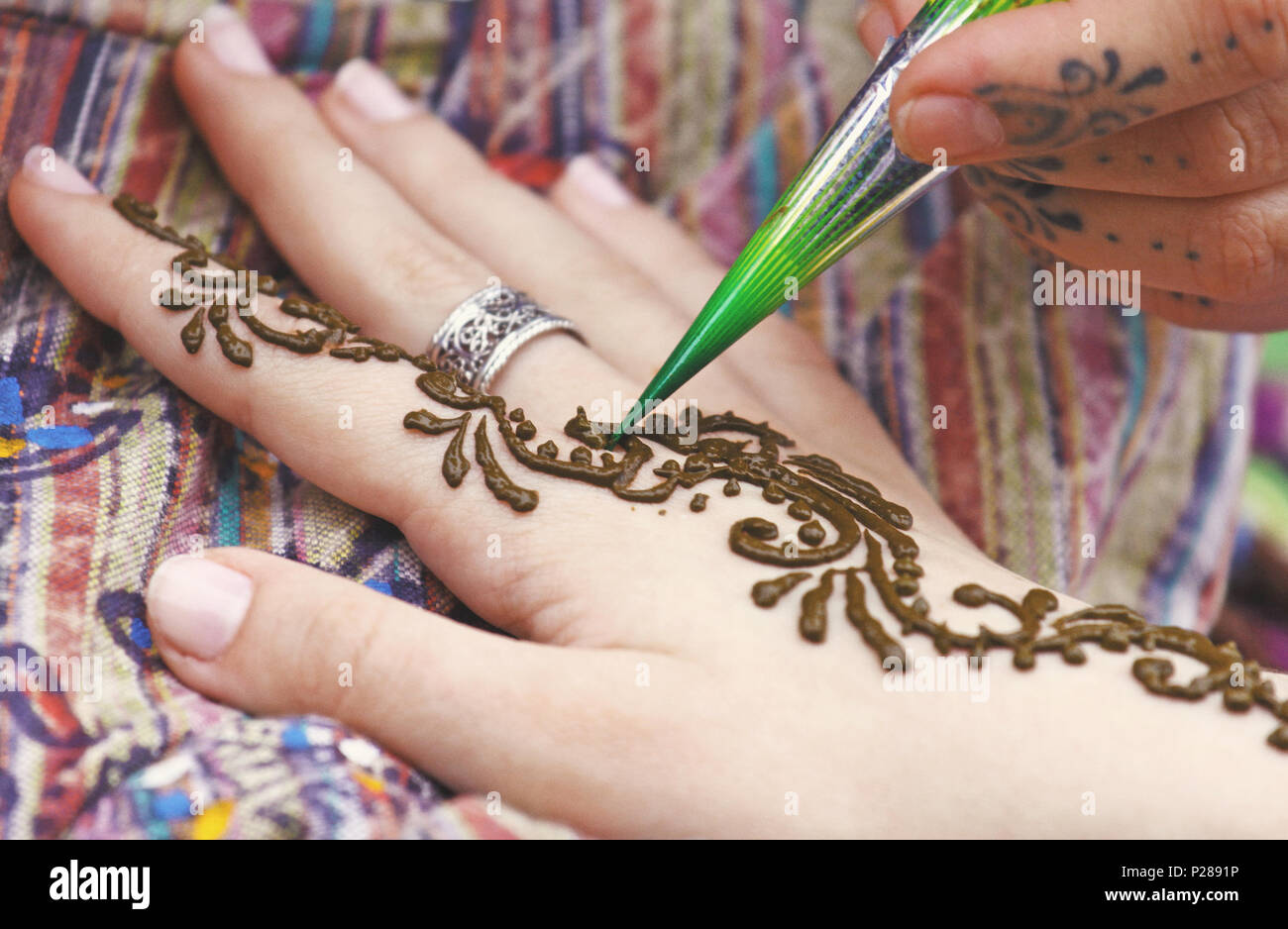 ed29d79e0 Artist painting traditional indian henna tattoo on woman hand, closeup  picture, focus on mehndi artwork