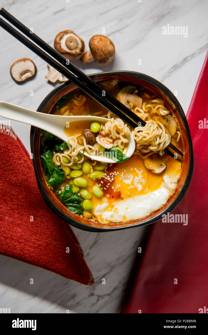 Spicy edamame and narutomaki spiral ramen noodle soup with runny fried egg - Stock Image