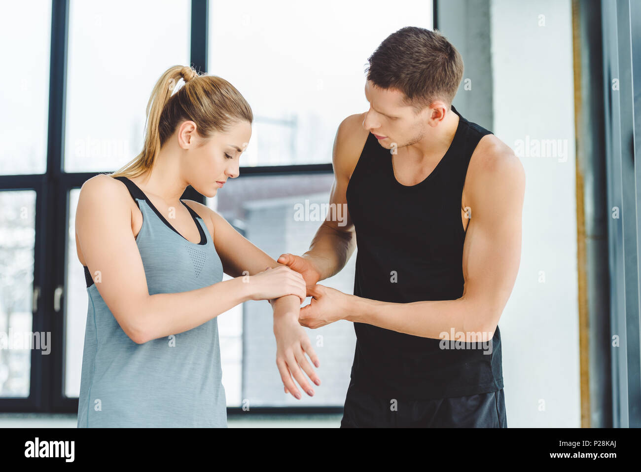 portrait of trainer holding injured arm of woman in gym - Stock Image