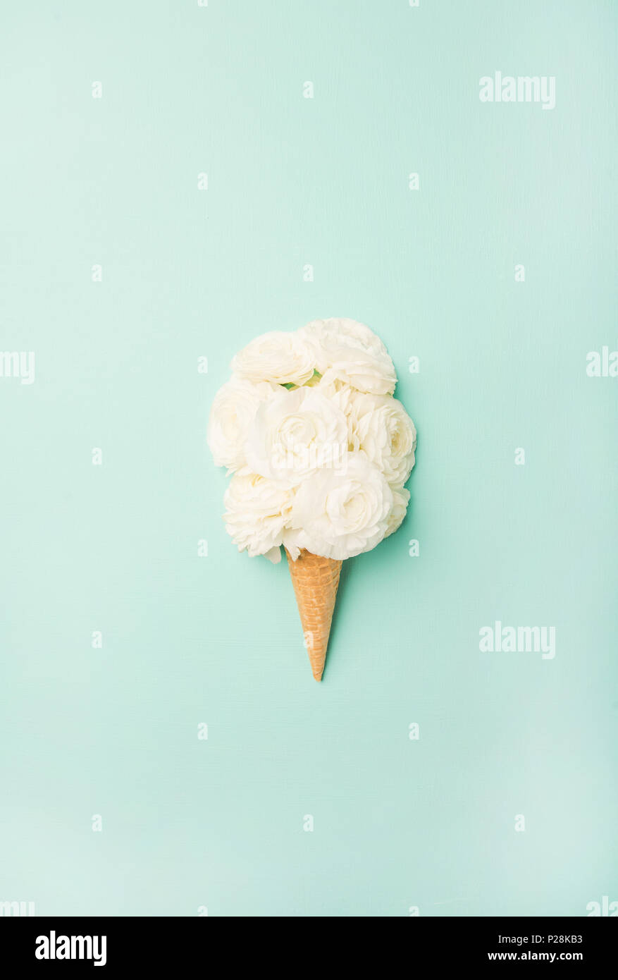 Waffle cone with white flowers over blue background, top view - Stock Image